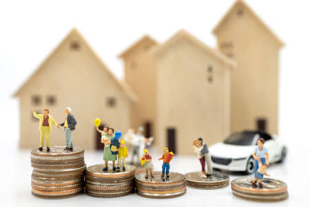 Miniature people: Elderly person and family standing on coins stack with home, Retirement planning concept. Stock Photo