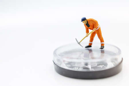 Miniature worker digging on compass. Concept of finding direction and opportunity. Stock Photo