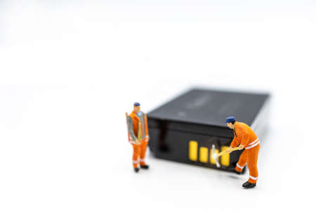 Miniature worker digging on battery. Concept of search for renewable energy or new energy. Stock Photo