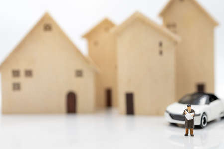 Miniature people:  Businessman reading book with house and car.  Concept of investment in housing and vehicles. Stock Photo