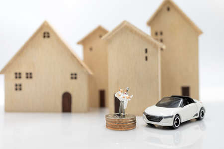 Miniature people: Couple in wedding dresses stand on coins stack with house and car. Family planning and housing concept. Stock Photo