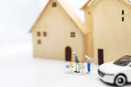 Miniature people: Parent and children with shopping cart standing on coins stack with house and car.  Concept of shopping in housing and vehicles. Stock Photo