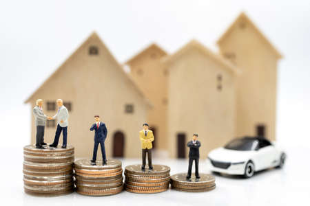 Miniature people:  Businessmen shaking hands on coins stack with house and car.  Concept of investment in housing and vehicles.