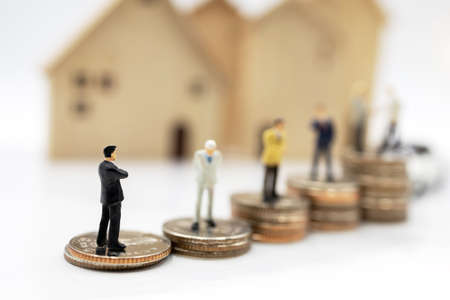 Miniature people:  Businessmen standing on coins stack with house and car.  Concept of investment in housing and vehicles. Stock Photo