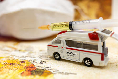 Syringe of COVID-19 vaccine on ambulance car with medical mask and world map background . Vaccine and Healthcare Medical concept. Stock Photo