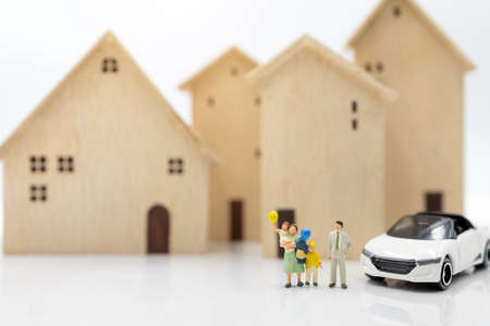 Miniature people: Parent and children standing with house and car. housing plan and family concept.