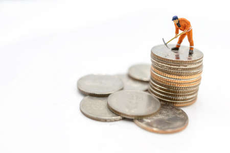 Miniature worker digging on coins stack. Concept of Money and investment. Stock Photo