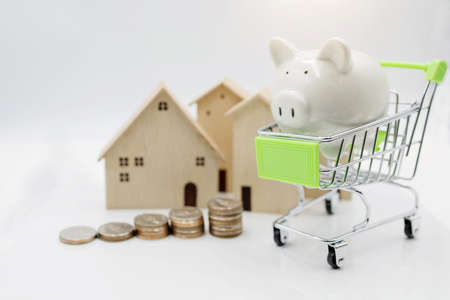Piggy bank on shopping cart with coins stack and house.  Concept of investment in housing.