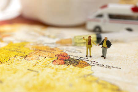 Miniature people stand on world map with ambulance car, medical mask and Syringe of COVID-19 vaccine . Vaccine and Healthcare Medical concept. Stock Photo