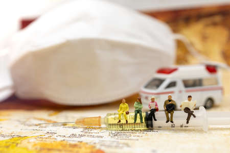 Miniature people sit Syringe of COVID-19 vaccine with ambulance car and medical mask and  . Vaccine and Healthcare Medical concept.