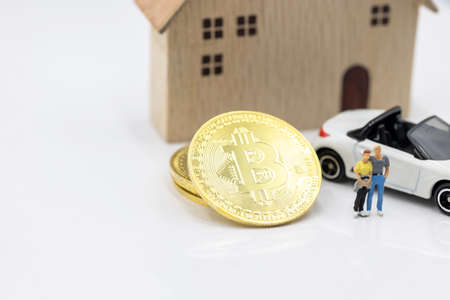 Miniature people standing with Gold bitcoin, house and car.  Concept of Business, Money, Technology, cryptocurrency and Investment.