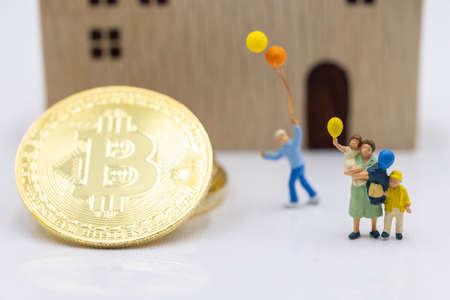 Miniature people standing with Gold bitcoin and house.  Concept of Business, Money, Technology, cryptocurrency and Investment.