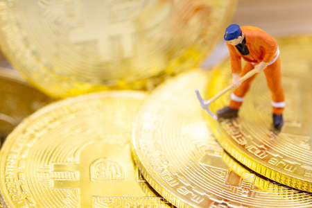 Miniature people miner figure working on Gold bitcoin.  Concept of Business, Money, Technology, cryptocurrency and Investment.