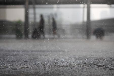 Gocce di pioggia nell'acqua pesante sull'ombra dell'asfalto di ombra nera e riflesso del cielo scuro in città. alto contrasto durante l'autunno