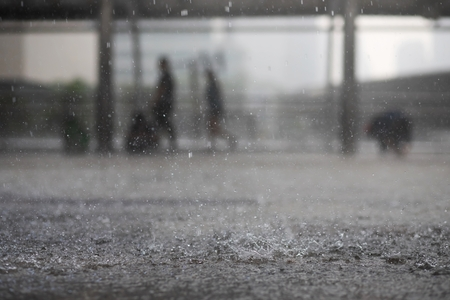 Gotas de lluvia en el agua pesada sobre asfalto sombra de sombra negra y reflejo del cielo oscuro en la ciudad. alto contraste durante el otoño
