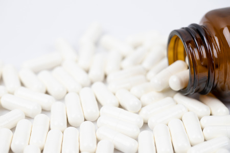 Pill bottle spilling out. capsule pills on to surface tablets on white background. drug medical healthcare concept