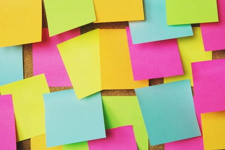 collection of colorful variety post it. paper note reminder sticky notes pin on cork bulletin board. empty space for text.