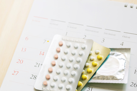 Contraceptive control pills and condoms on date of calendar calculate date Control the birth rate. table wood background. health care and medicine, contraception concept. empty space for text.