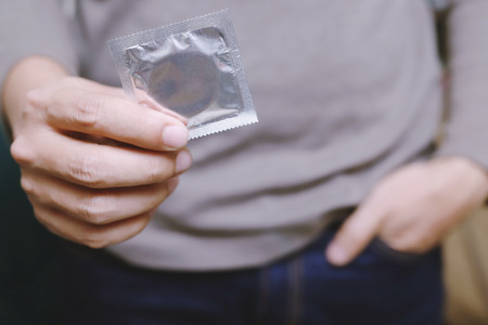 Condom ready to use in young man hand, give condom safe sex concept on the bed Prevent infection and Contraceptives control the birth rate or safe prophylactic. World AIDS Day, Leave space for text.
