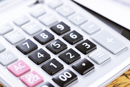 calculator focus at on press button keyboard. calculator color gray and documents pen on table. concept calculate account finance. Stock Photo