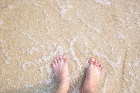 Closeup of a mans bare feet stand at wet on the beach , with a waves edge foaming gently beneath them. Vacation on ocean beach, foot on sea sand. Leave empty copy space Enter the text above.