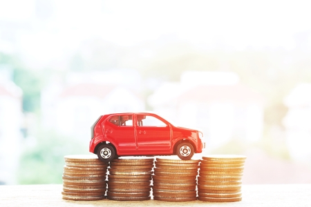 Little red car over a lot of money stacked coins with isolated white background . for loans costs finance concept. empty copy space for text.
