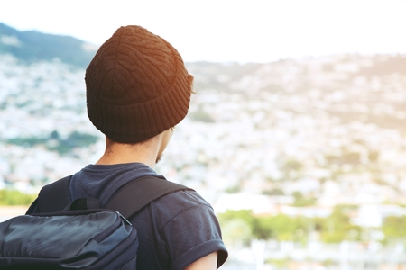 Traveling tourist man Backpack looking at amazing tropical mountains forest Scenic views city country.