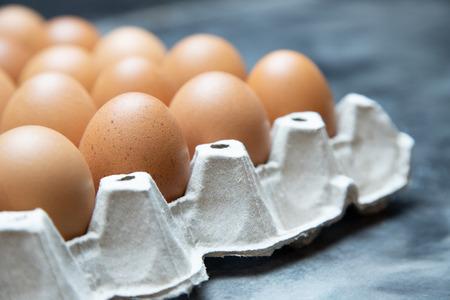 hele eieren in doos. Kippenei op tafel. Stockfoto