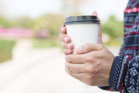 young man hand holding Paper cup of take away drinking coffee hot on natural morning.