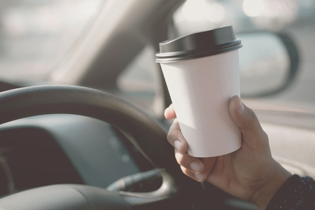 people person drinking paper cup coffee of hot in hand while driving in a car in the morning .transportation and vehicle concept.