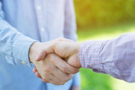 homme d'affaires serrer la main entre deux collègues Chemise à carreaux. ou Négocier un accord.Bonne affaire. Gros plan sur la poignée de main. Affaires fluides. toutes nos félicitations Banque d'images