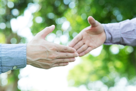 Closeup of a business hand shake between two colleagues greet , Represents Friendship is good,success, congratulations. outdoor of building background. copy leave space for text. Banco de Imagens