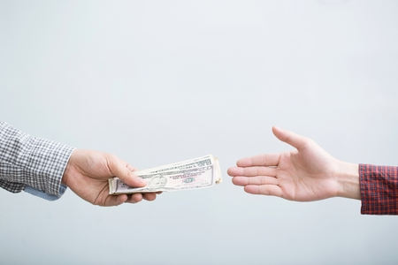 close up Business man hand holding giving money isolated on white background. Paid for by Cash in Business Concept.