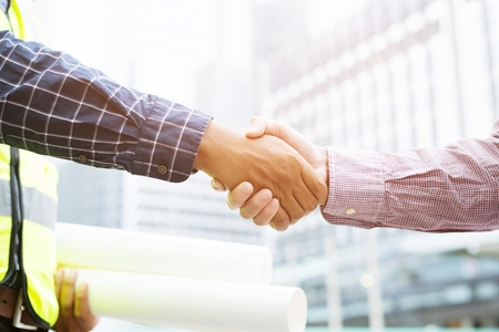 Close up of a engineering male holding document plan Construction project worker hand shake between two business man, Represents is good project success approve, congratulations. outdoor of building.