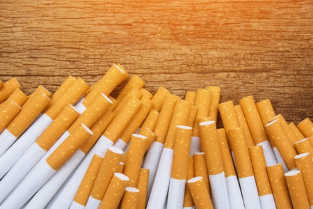 A top view image of several commercially made cigarettes. pile cigarette on wooden. or Non smoking campaign concept