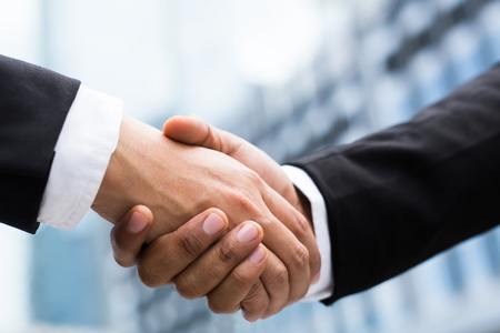 companionship hand clasping success trust, confident concept. or Closeup of a businessman hand between two colleagues on outdoor building. Stock Photo