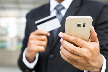 business man holding credit card and using phone. Online shopping purchase Sell or Payment.