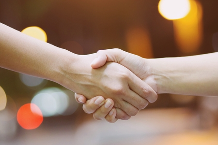 Closeup of a business hand shake between two colleagues in business at night.
