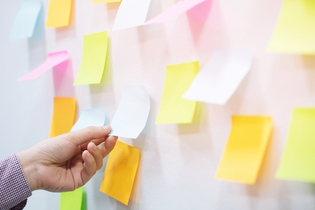 close up hand people business man sticky notes notes in the wall at meeting room. Sticky note paper reminder schedule board. Colorful variety copy empty space. soft focus. Stock Photo