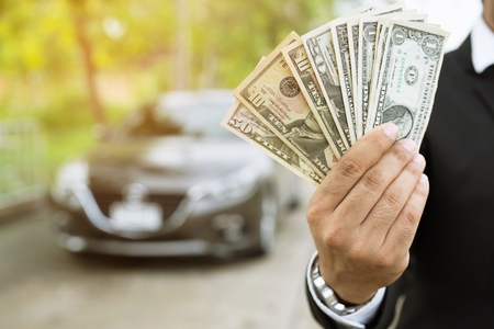 Business man holding money in hand stand front car prepare pay by installments - insurance, loan and buying car concept Banco de Imagens