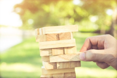 Game jenga, Close up of people mans hand playing take one block wood stack game on the tower in outdoor, concept Planning risk and strategy in businessman and engineer. Banco de Imagens