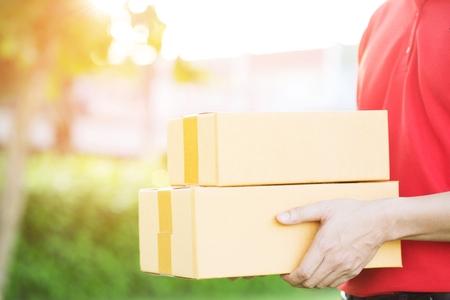 uomo di consegna pacchi di un pacco attraverso un servizio. e cliente ravvicinato che accetta una consegna di scatole dal fattorino postale. Archivio Fotografico