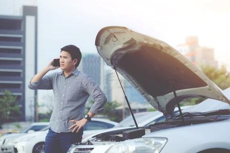 Wütender Mann steht vor einem kaputten Auto und ruft nach einem Notruftelefon.