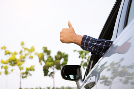 Man traveler ready to leave drive a car on the road. showing hand thumb up outdoor. Zdjęcie Seryjne