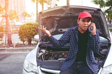 young stressed man having trouble with his Stress broken car Engine room crash at failed engine Wait for help.