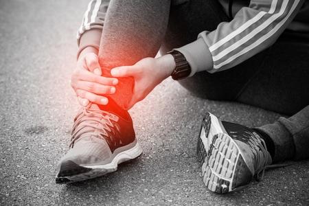 Coureur touchant une cheville tordue ou cassée douloureuse. Accident d'entraînement de coureur d'athlète. L'entorse de la cheville en cours de course sportive cause des blessures.