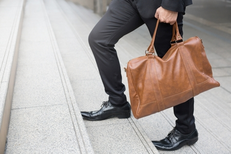 Businessman with briefcase brown leather bag walking upstairs ,Fighting against obstacles Climb up to Successful finish concept. Banque d'images