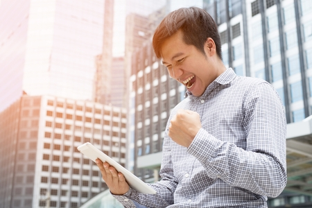 Investor young businessman standing using a laptop tablet and Holds a fist win stock market stock emotionally up very happy mood Get profit.