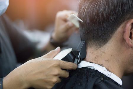 Person Mann Haarschnitt bekommt stilvolle Haare Vintage Rasur, mit Rasiermesser von Friseur Friseur mit Händen im Friseursalon.