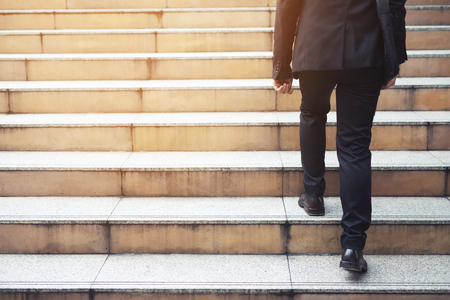 businessman legs walking the stairs in modern city.